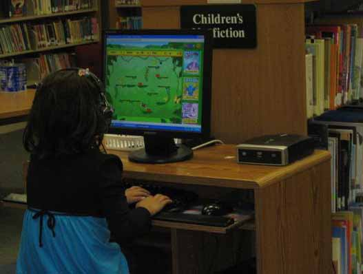 Girl playing on a computer in the library